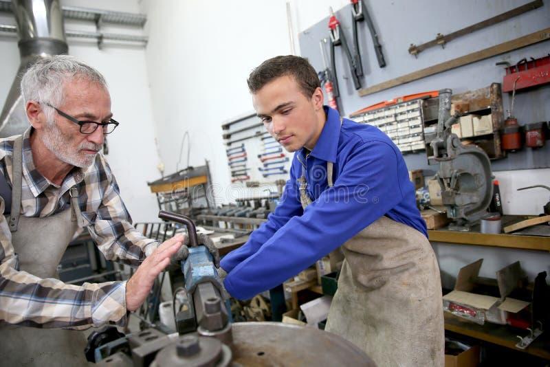 Giovane che impara le industrie siderurgiche con l'istruttore fotografie stock