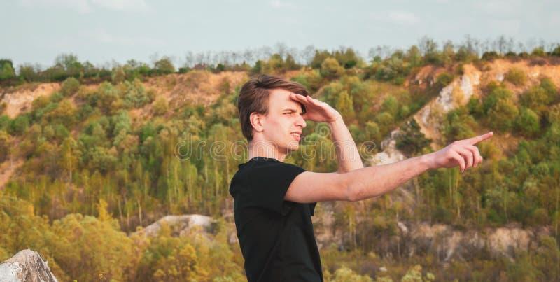 Giovane che indica la direzione con il suo dito mentre facendo un'escursione nelle montagne, foto orizzontale immagine stock