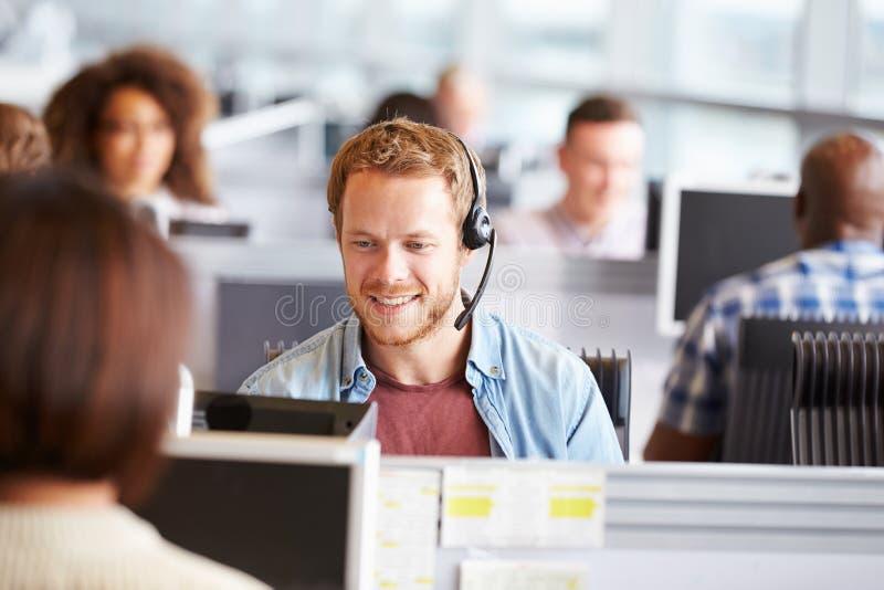 Giovane che lavora ad un computer in un call-center immagine stock