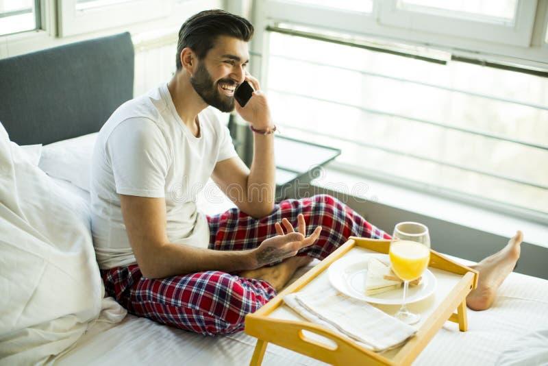 Giovane che mangia prima colazione a letto e che per mezzo di un telefono cellulare fotografia stock libera da diritti