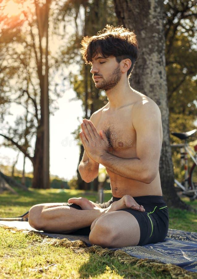 Giovane che medita nel parco nella posizione del loto immagine stock