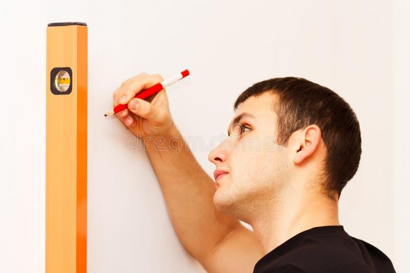 Giovane che misura a livello e che fa il contrassegno della matita immagine stock