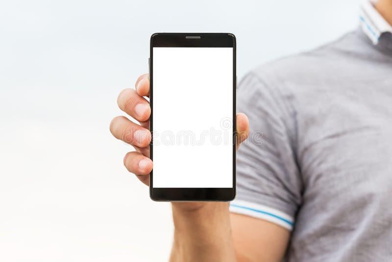 Giovane che mostra un'applicazione del telefono cellulare fotografia stock libera da diritti