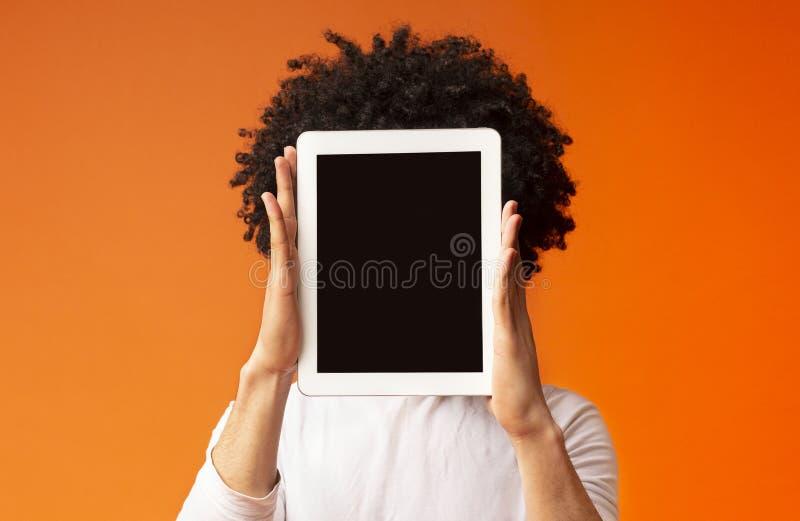 Giovane che nasconde il suo fronte dietro la compressa digitale immagini stock