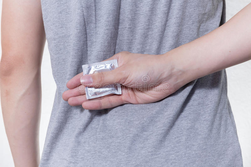 Giovane che nasconde un preservativo sul suo controllo delle nascite retro-/HIV e fotografia stock libera da diritti
