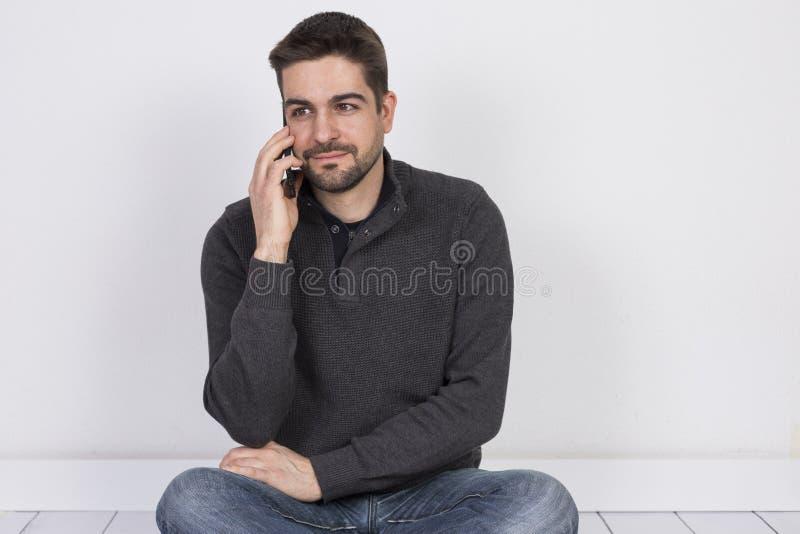 Giovane che parla sul suo telefono cellulare Priorit? bassa bianca Tecnologia e stile di vita immagine stock