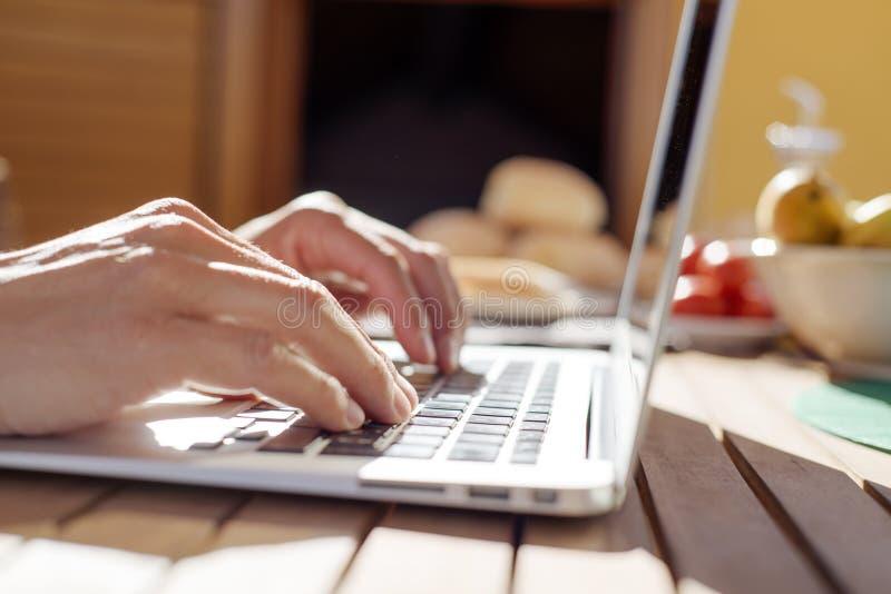 Giovane che per mezzo di un computer portatile all'aperto immagine stock libera da diritti
