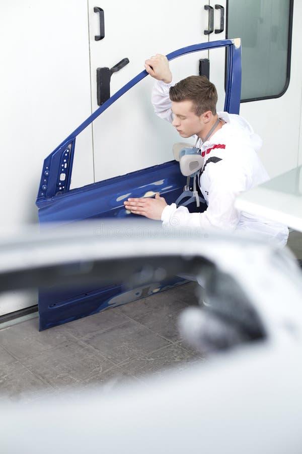Giovane che ripara porta in automobile immagine stock