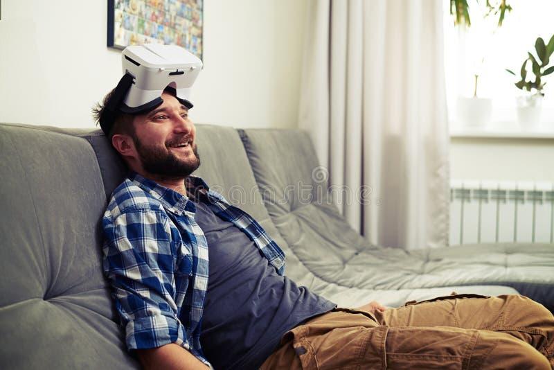 Giovane che riposa dopo il gioco dei giochi di computer di realtà virtuale fotografia stock