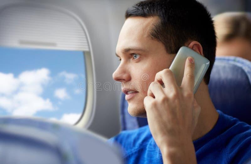 Giovane che rivolge allo smartphone in aereo immagine stock libera da diritti