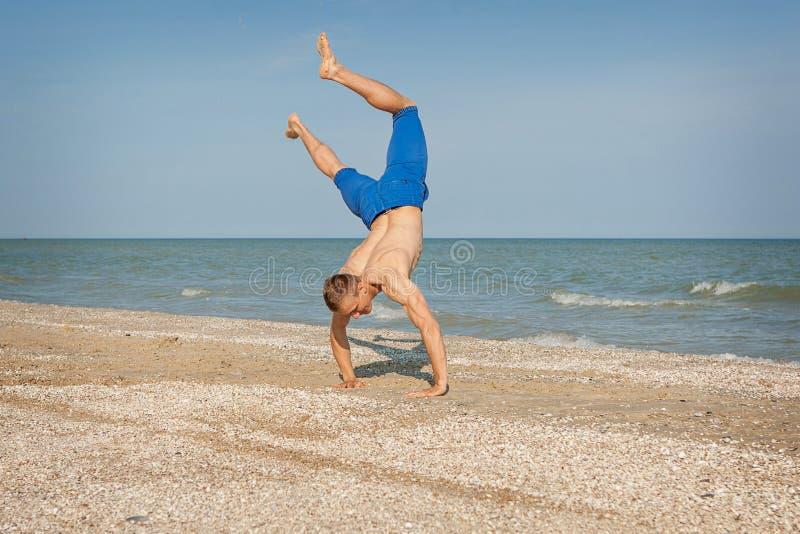 Giovane che salta sulla spiaggia immagini stock