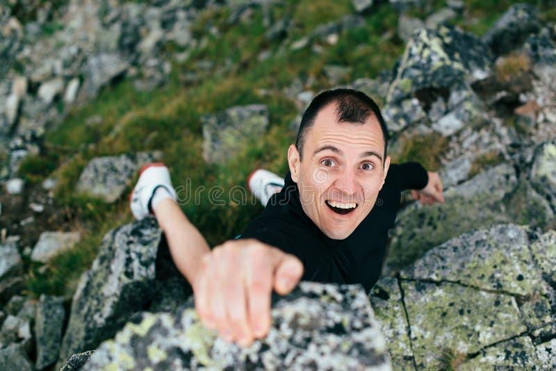 Giovane che scala una parete ripida in montagna Arrampichi lo sport estremo Uomo turistico che fa un'escursione e che scala alle  immagine stock