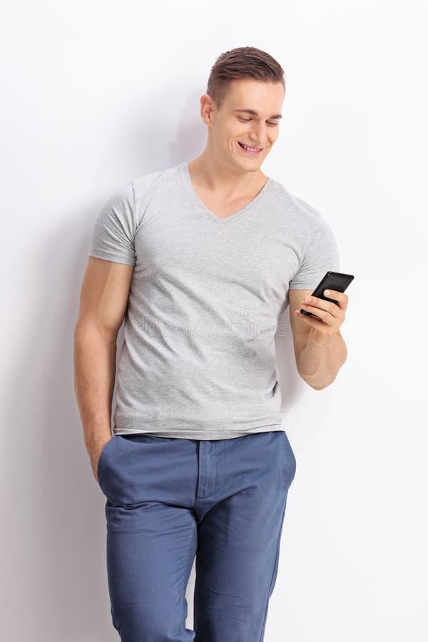 Giovane che scrive SMS a macchina sul suo telefono cellulare immagine stock libera da diritti