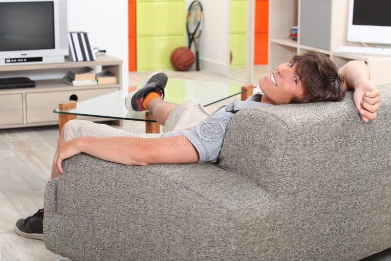 Giovane che si rilassa sul sofà fotografie stock