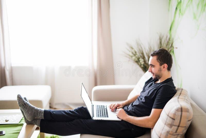 Giovane che si rilassa sul sofà con un computer portatile a casa immagini stock