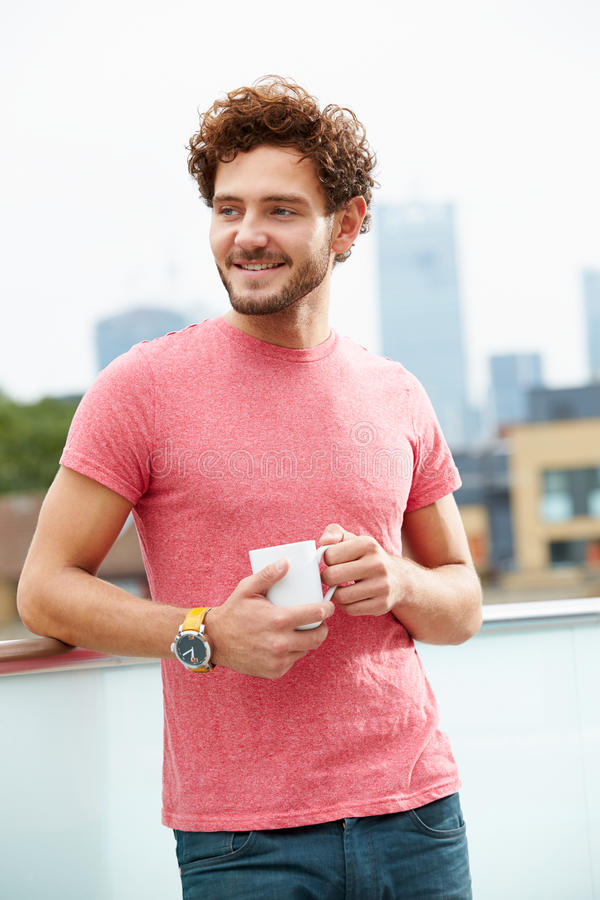 Giovane che si rilassa sul terrazzo del tetto con la tazza di caffè fotografia stock