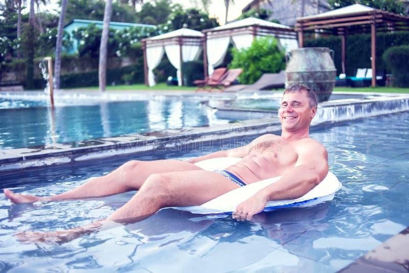 Giovane che si rilassa sulla ciambella gonfiabile nella piscina Estate immagini stock libere da diritti