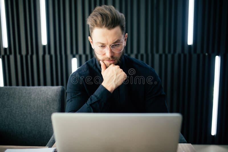 Giovane che si siede alla tavola che distoglie lo sguardo e che pensa Ufficio di seduta dell'uomo d'affari premuroso fotografie stock libere da diritti