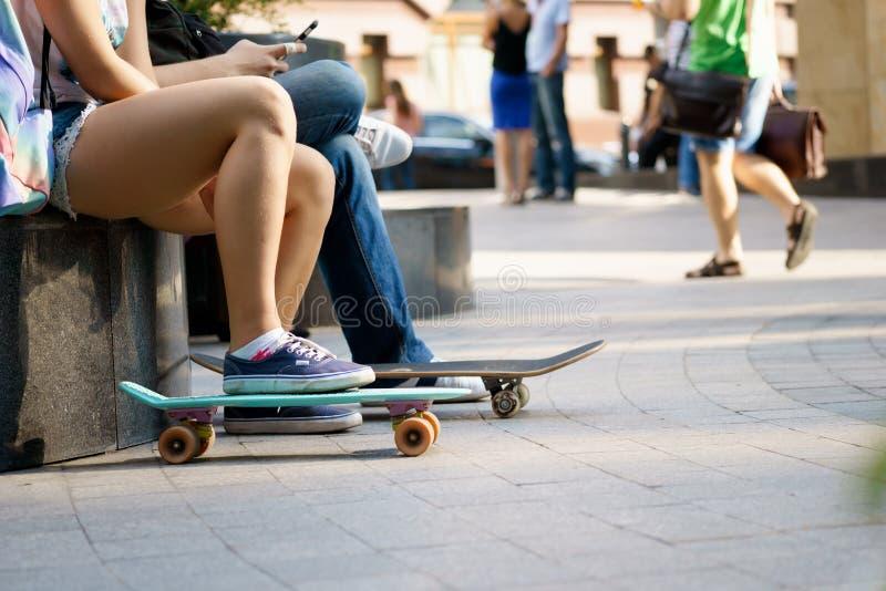 Giovane che si siede con i pattini e che riposa il giorno di estate fotografia stock libera da diritti
