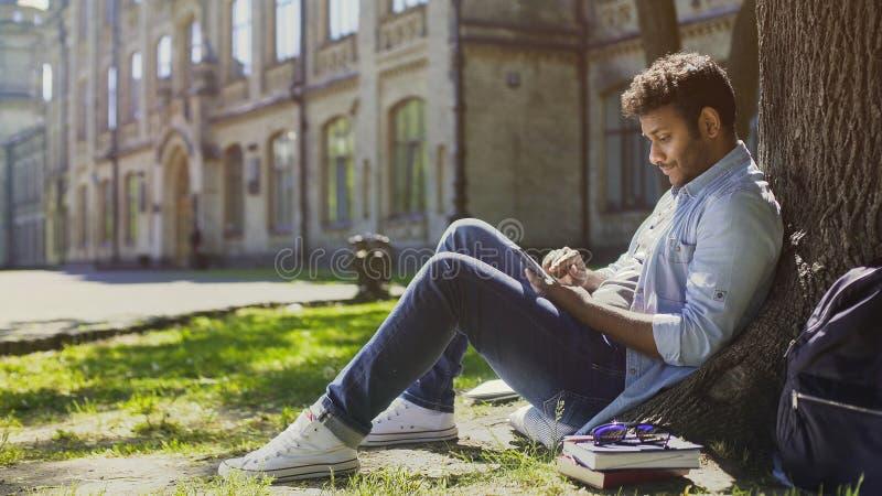 Giovane che si siede sotto l'albero in parco, facendo uso del telefono cellulare e sorridente, buone notizie fotografie stock