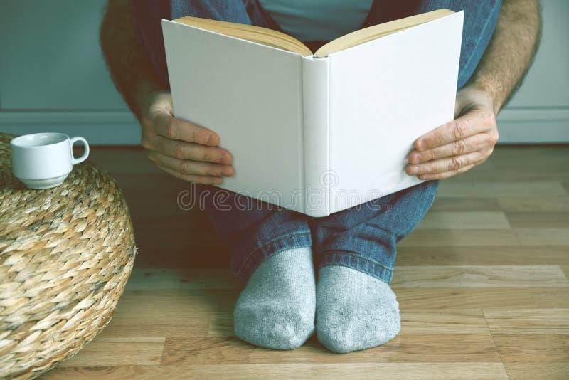 Giovane che si siede sul caffè bevente del pavimento di legno mentre leggendo un libro spazio vuoto della copia fotografia stock libera da diritti