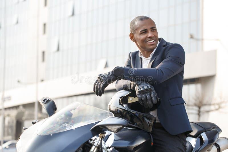Giovane che si siede sul motociclo nei guanti di sport che guardano da parte felici fotografia stock