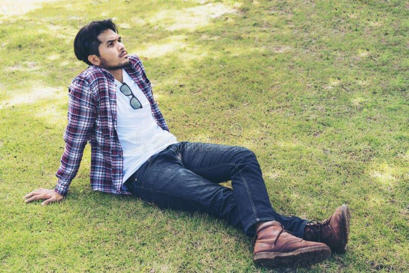 Giovane che si siede sul pensiero dell'erba verde fotografia stock libera da diritti