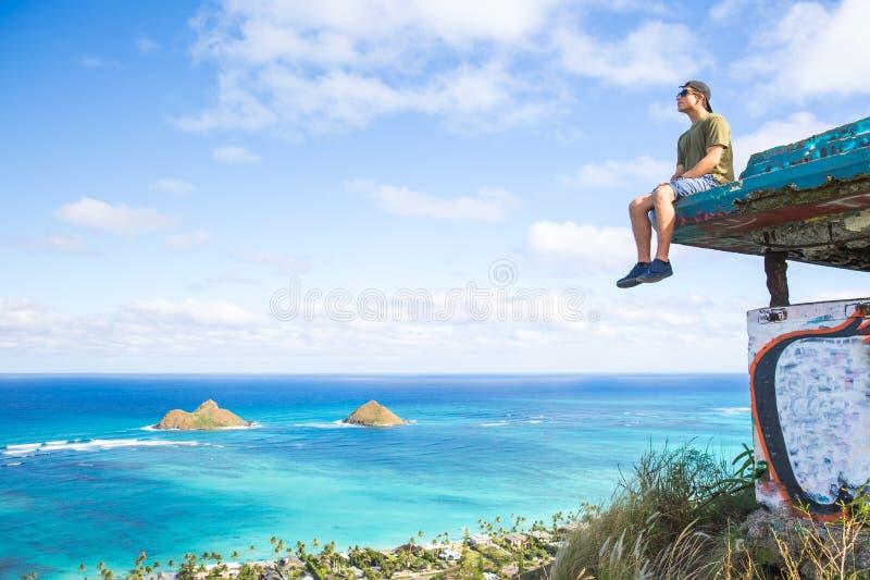Giovane che si siede sulle portapillole sopra lo sguardo del Lanikai che guarda fuori OV fotografia stock
