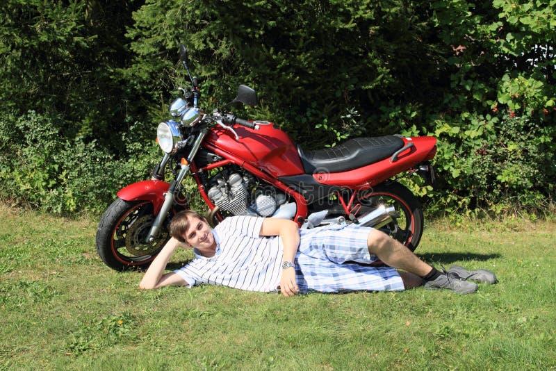 Giovane che si trova davanti alla motocicletta fotografia stock libera da diritti