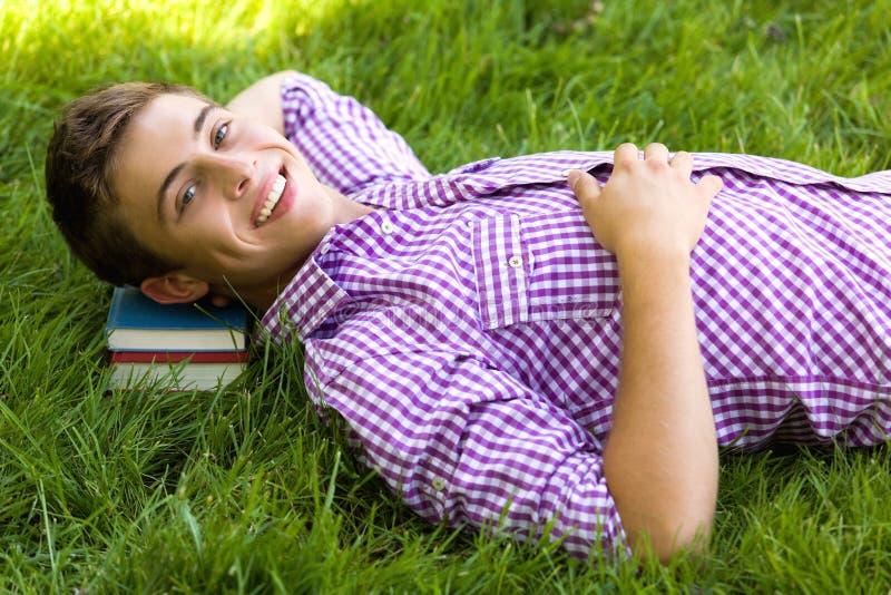 Giovane che si trova su un mucchio dei libri immagini stock