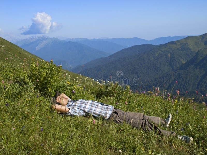 Giovane che si trova sull'erba in montagne in sole immagine stock