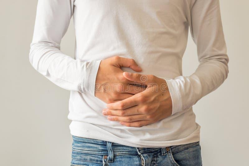 Giovane che soffre dalla diarrea di dolore di stomaco, costipazione, riflusso acido, indigestione, nausea immagini stock libere da diritti