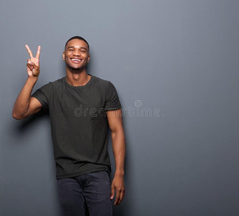 Giovane che sorride mostrando il segno di pace della mano fotografie stock libere da diritti