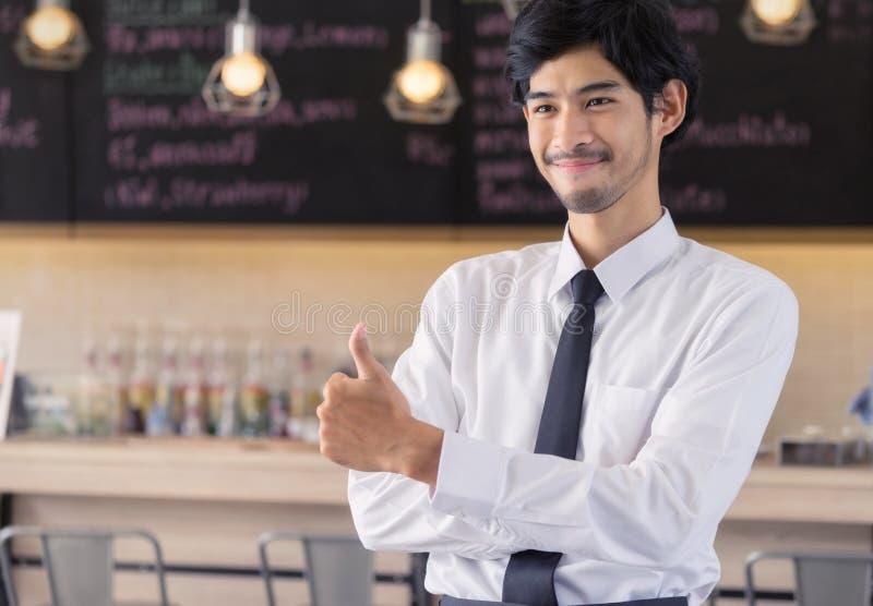 Giovane che sta al contatore del caffè Maschio al lavoro in caffè SH immagini stock libere da diritti