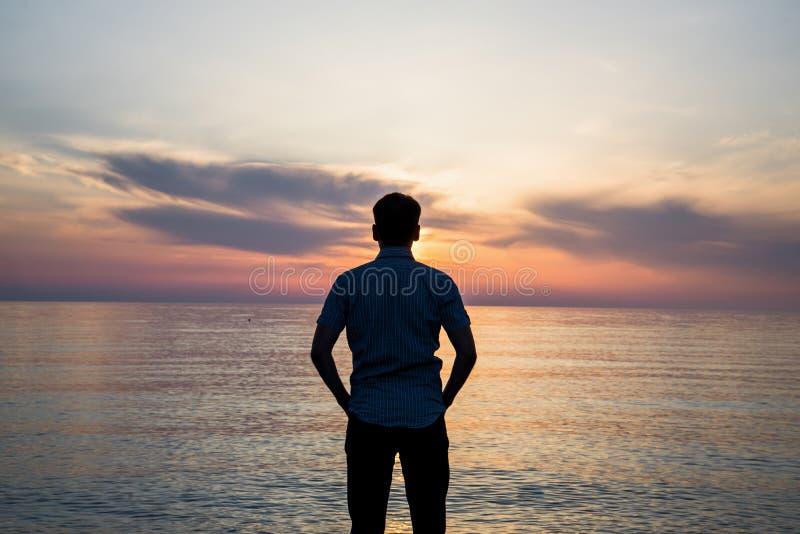 Giovane che sta alla spiaggia davanti alla vista stupefacente del mare al tramonto o all'alba e che pensa al suo futuro rear fotografie stock