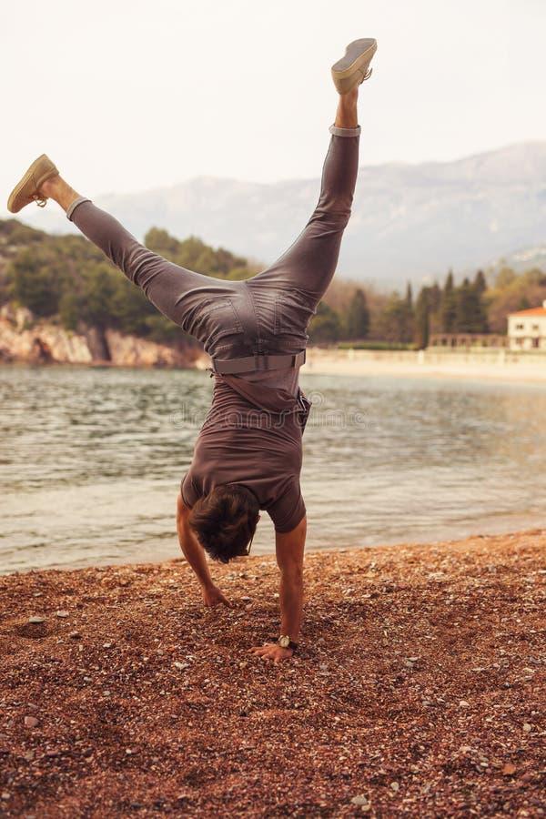 Giovane che sta sulle sue mani dal mare sulla spiaggia fotografie stock libere da diritti