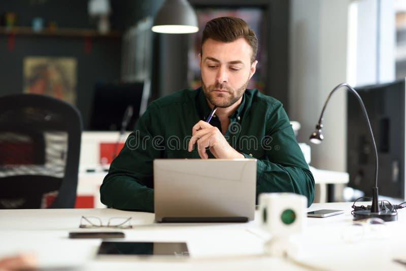 Giovane che studia con il computer portatile sullo scrittorio bianco immagine stock