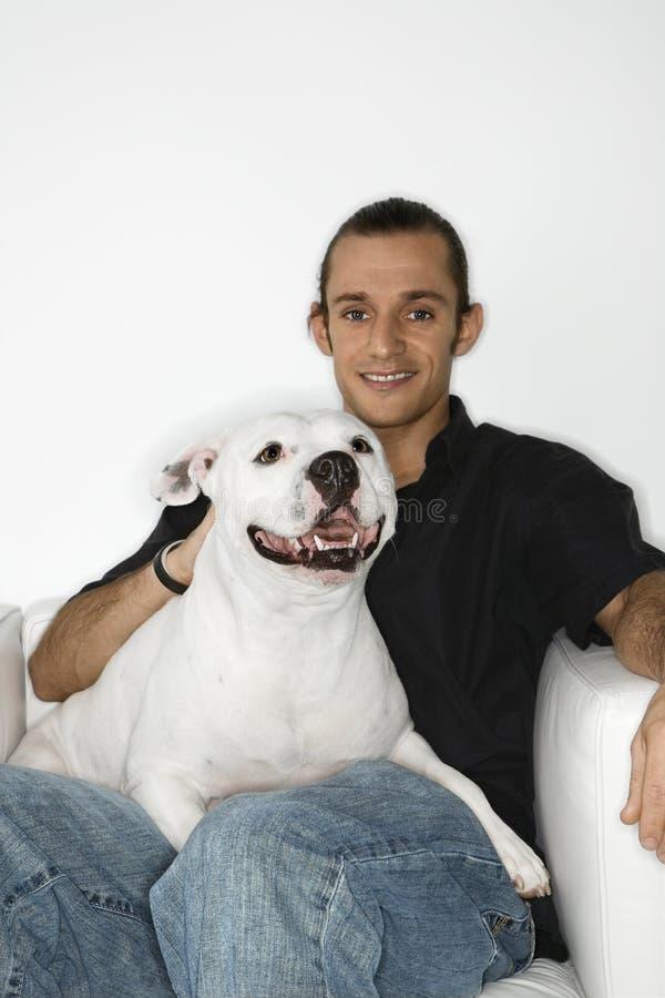 Giovane che tiene cane bianco sul giro. fotografia stock