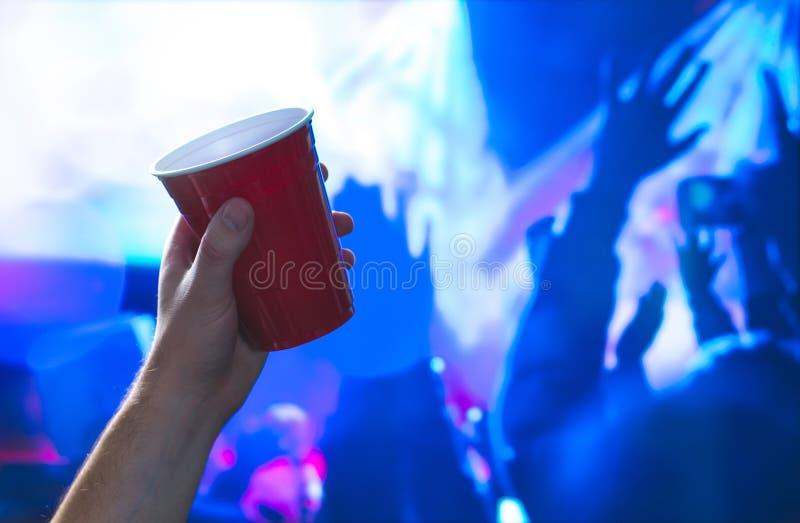 Giovane che tiene la tazza rossa del partito nella pista da ballo del night-club Contenitore dell'alcool a disposizione in discot immagini stock libere da diritti