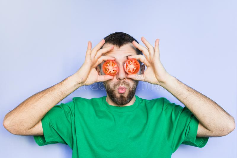 Giovane che tiene le fette di pomodori rossi davanti ai suoi occhi immagine stock libera da diritti