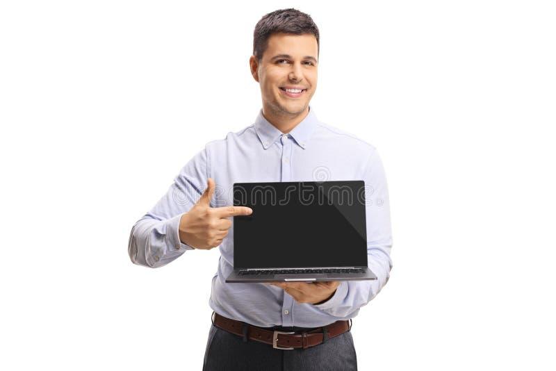 Giovane che tiene un computer portatile e che indica lo schermo immagini stock libere da diritti