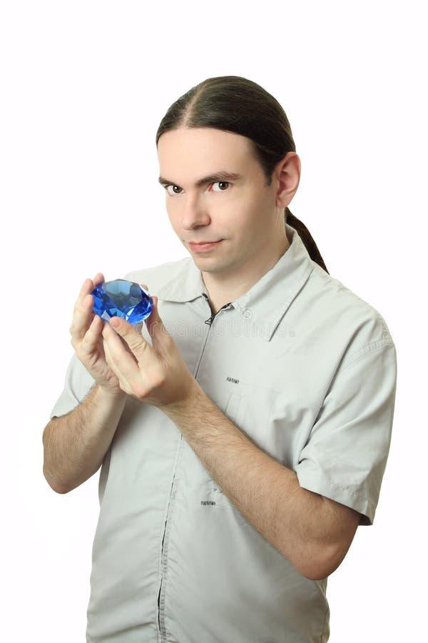 Giovane che tiene un cristallo immagine stock