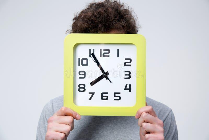 Giovane che tiene un grande orologio che copre il suo fronte fotografia stock libera da diritti