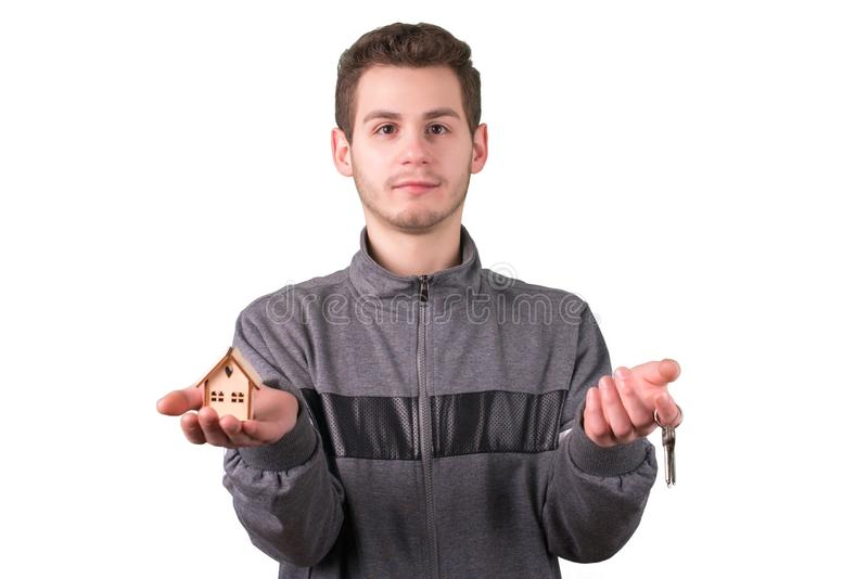 Giovane che tiene una piccola casa di legno e le chiavi Isolato su bianco fotografie stock