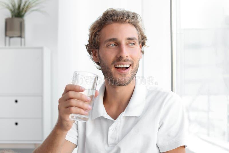 Giovane che tiene vetro di acqua pulita fotografia stock libera da diritti