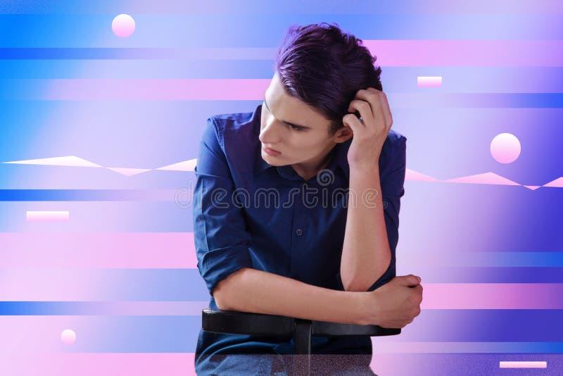 Giovane che tocca la sua testa e che sembra preoccupato fotografia stock libera da diritti