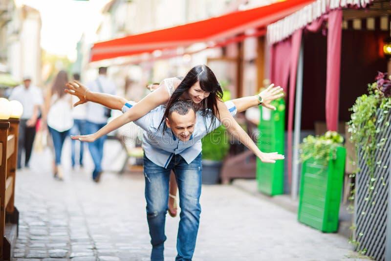 Giovane che trasporta sulle spalle la sua amica felice con la mano sollevata Gli amanti allegri che sognano, camminano la città fotografie stock