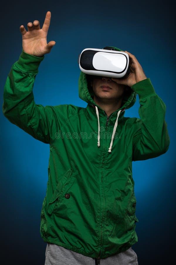 Giovane che usando i vetri di una cuffia avricolare di VR Uomo con i vetri di realtà virtuale che mostrano gesto Colpo dello stud fotografie stock libere da diritti