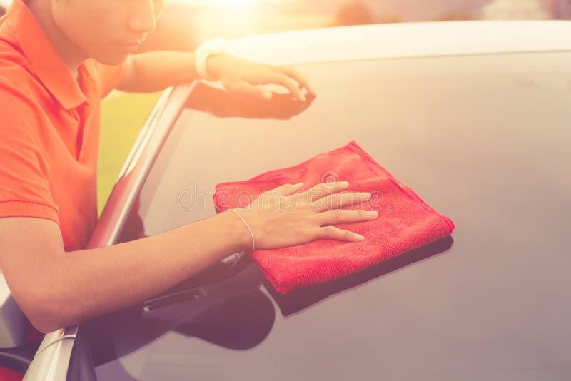 Giovane che usando l'ente rosso di pulizia del panno del microfiber di nuovo argento fotografia stock
