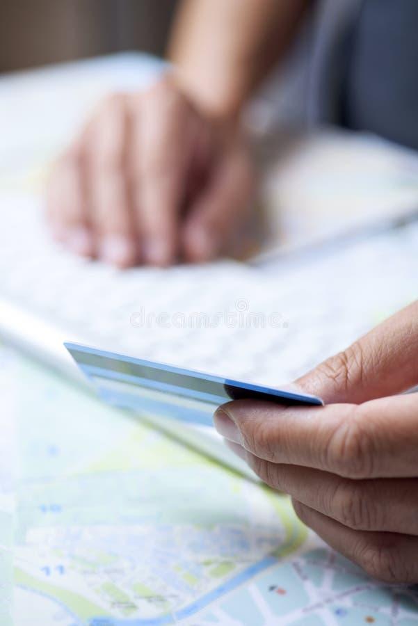 Giovane che usando una carta di credito per prenotare un viaggio immagini stock libere da diritti